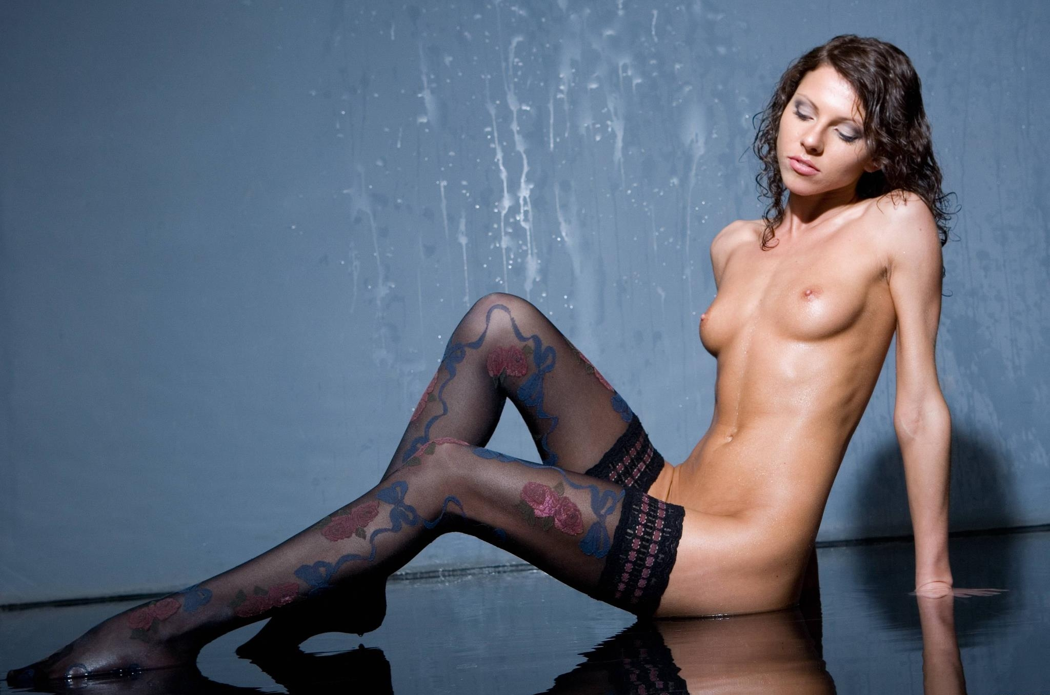 brunette naked young girl in wet black pattern stockings